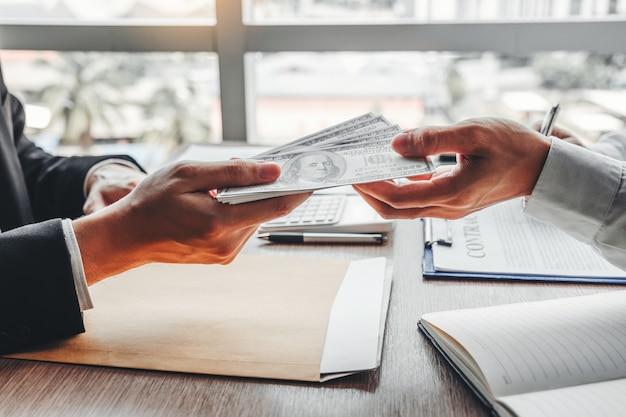 , zakenman die dollarrekeningen geeft aan bedrijfsleider om contract te behandelen