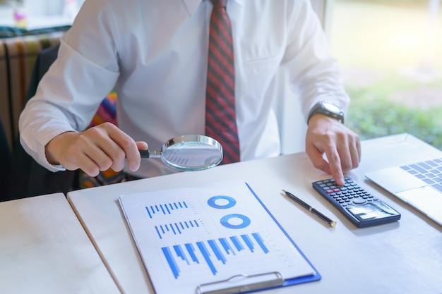 Zakenman die door een vergrootglas kijkt aan bedrijfsgrafiekrapport en calculator gebruikt.