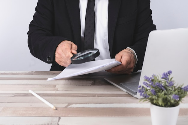 Zakenman die door een vergrootglas naar documenten kijkt