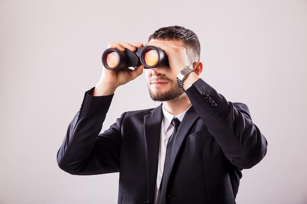 Zakenman die door een verrekijker kijkt die op witte muur wordt geïsoleerd