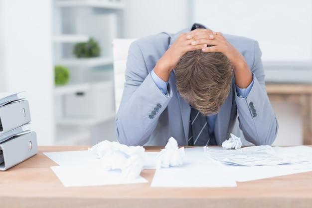 Zakenman die door te werken wordt gedeprimeerd