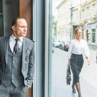 Zakenman die door venster kijkt terwijl vrouw die op stoep loopt