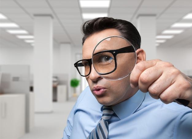 Zakenman die door vergrootglas kijkt, de financiële papieren van het offshore bedrijf inspecteert,