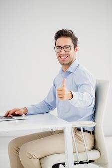 Zakenman die duimen toont terwijl het gebruiken van laptop