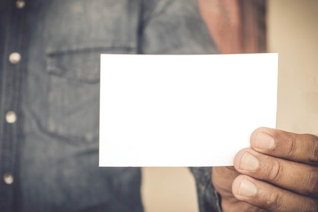 Zakenman die een adreskaartje houdt.