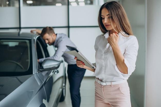Zakenman die een auto kiest met een verkoopster bij autosalon