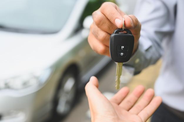 Zakenman die een autosleutel geeft. een nieuw autoconcept krijgen.