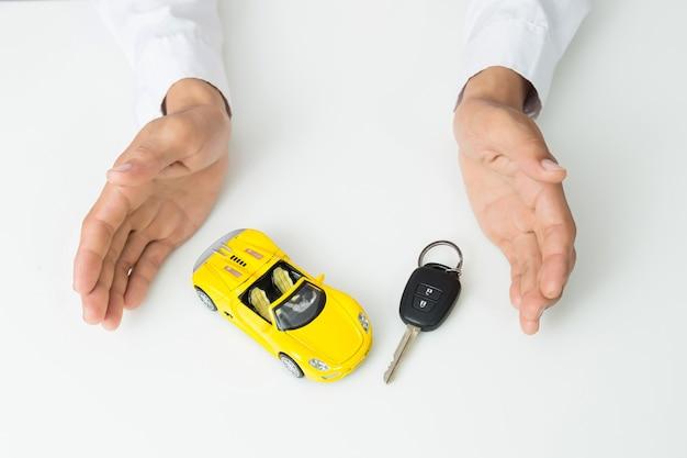 Zakenman die een autosleutels en een miniatuurautomodel houden