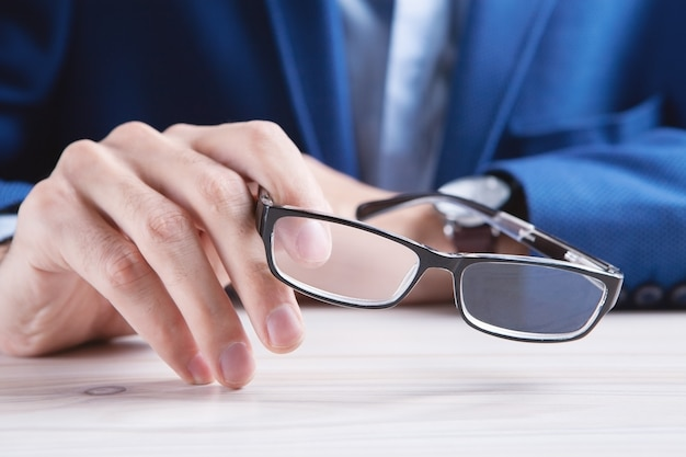 Zakenman die een bril gaat nemen om te lezen