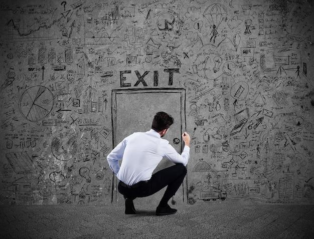 Zakenman die een deur op de muur trekt. ontsnap aan zakelijke stress en financiële crisis