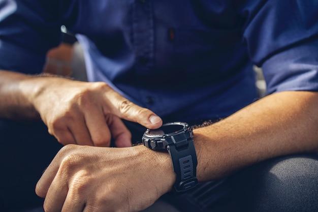 Zakenman die een digitaal slim horloge in de hand draagt en het scherm aanraakt om de melding te openen