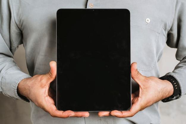 Zakenman die een digitaal tabletmodel houdt
