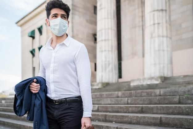 Zakenman die een gezichtsmasker draagt en een aktetas vasthoudt tijdens het wandelen naar het werk buitenshuis.