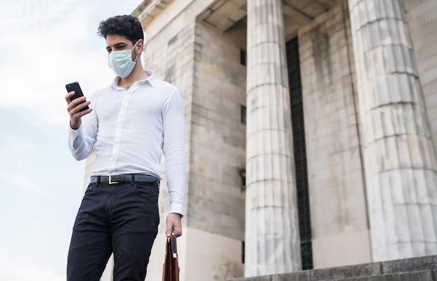 Zakenman die een gezichtsmasker draagt en zijn mobiele telefoon gebruikt tijdens het buiten lopen