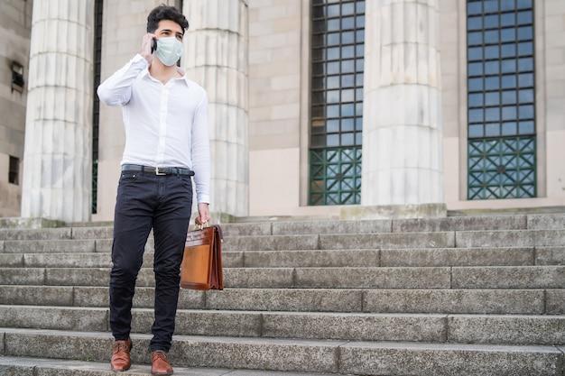 Zakenman die een gezichtsmasker draagt terwijl hij buiten aan de telefoon spreekt