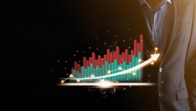 Zakenman die een groeiend virtueel hologram van statistieken, grafiek en grafiek met pijl omhoog op donkere achtergrond houdt en toont. beurs. bedrijfsgroei, schaven en strategieconcept.