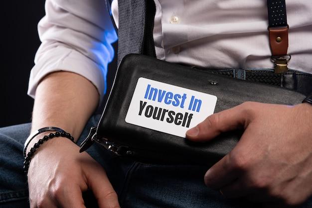 Zakenman die een kaart met de tekst invest in yourself zet.