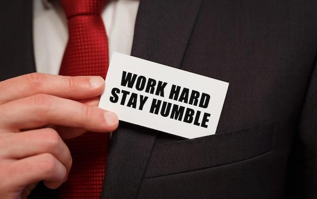 Zakenman die een kaart met de tekst work hard stay humble in de zak zet
