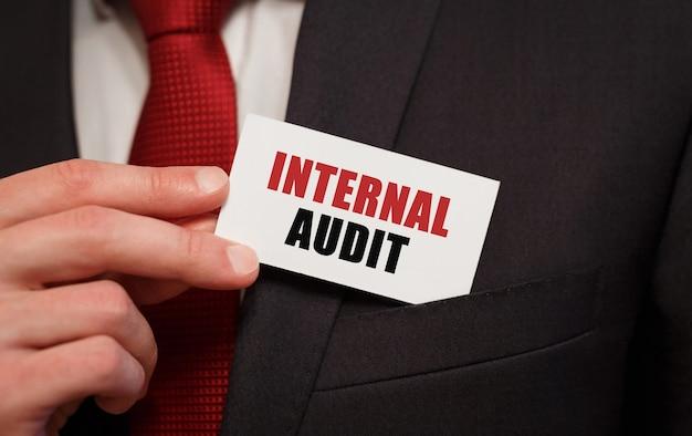 Zakenman die een kaart met tekst interne audit in de zak zet