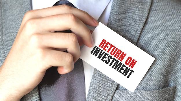 Zakenman die een kaart met tekstrendement op investering houdt
