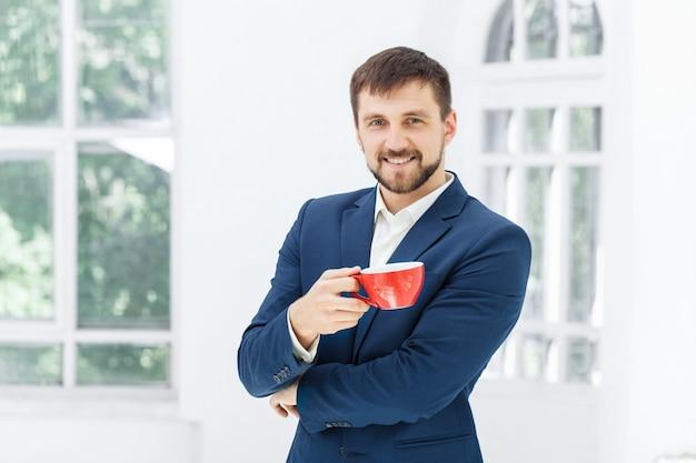 Zakenman die een koffiepauze heeft, houdt hij een rode kop