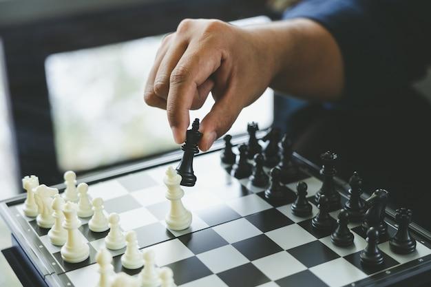 Zakenman die een koning schaken is geplaatst op een schaakbord
