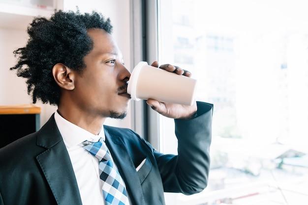 Zakenman die een kopje koffie drinkt terwijl hij een pauze neemt van zijn werk op zijn kantoor. bedrijfsconcept.