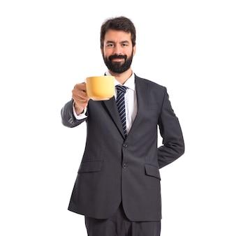 Zakenman die een kopje koffie op witte achtergrond houdt