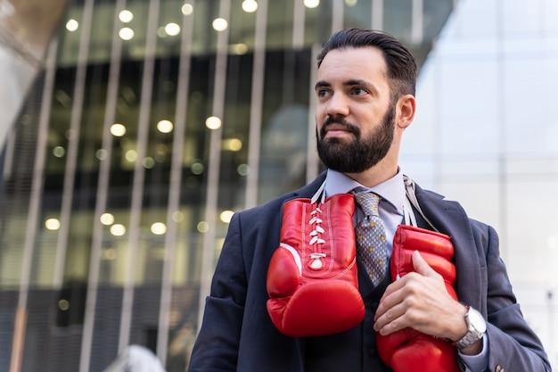 Zakenman die een kostuum draagt en rode bokshandschoenen raakt die van zijn hals hangen