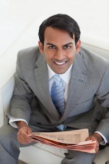 Zakenman die een krant leest en in een wachtkamer zit