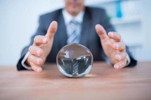 Zakenman die een kristallen bol voorspelt