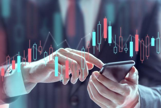 Zakenman die een mobiele telefoon met behulp van om effectenbeursgegevens, technische prijsgrafiek en indicator te controleren
