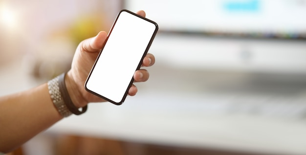 Zakenman die een mobiele telefoon met het witte scherm over het bureau in het bureau houdt