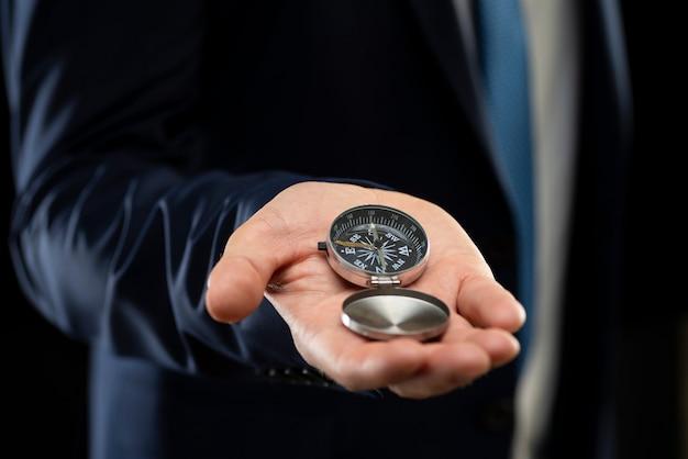Zakenman die een navigatiekompas in zijn hand houdt. bedrijfsplanning en bedrijfsnavigatie voor herstel, zodat zakenlieden de bedrijfsgroei hervatten tijdens de economische crisis.