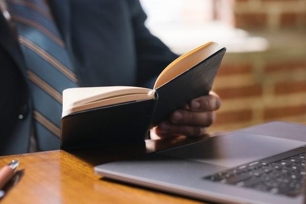 Zakenman die een notitieboekje leest op het werk