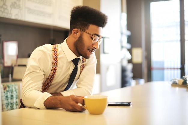 Zakenman die een onderbreking neemt, koffie drinkt terwijl het controleren van zijn telefoon