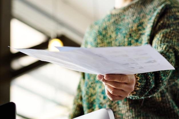 Zakenman die een papier overhandigt op kantoor