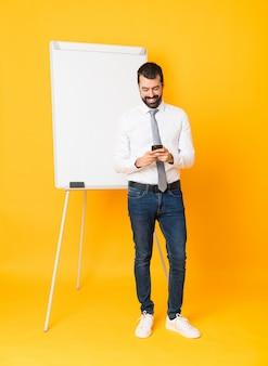 Zakenman die een presentatie geeft op wit bord een bericht verzendt met de mobiel