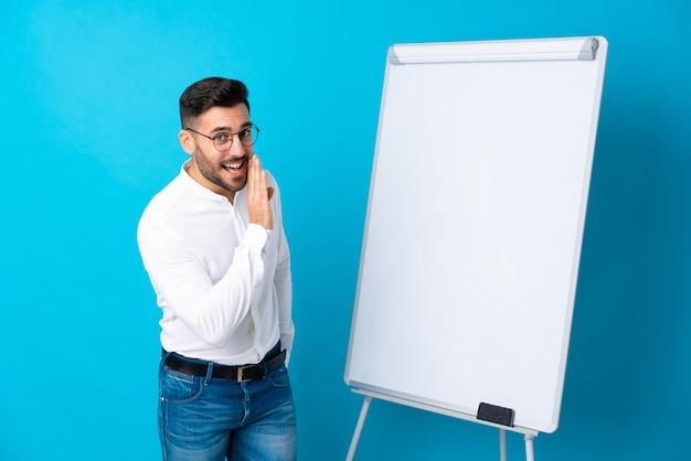 Zakenman die een presentatie op wit bord geeft en een presentatie op wit bord geeft en iets fluistert