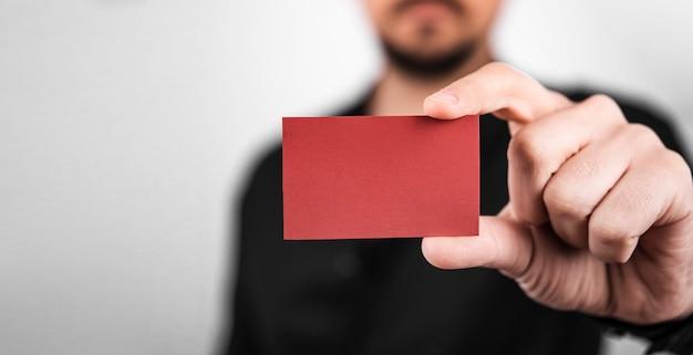 Zakenman die een rode lege bezoekkaart houdt