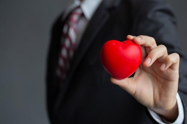 Zakenman die een rood hart houdt