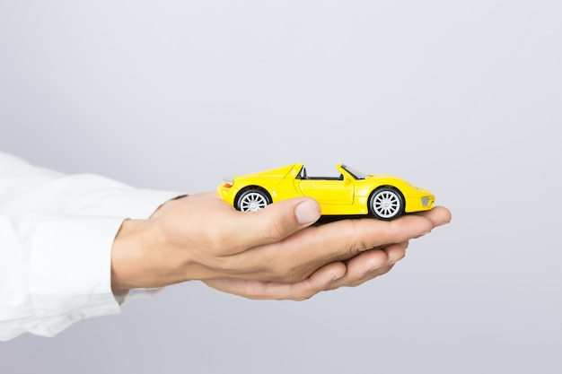 Zakenman die een stuk speelgoed auto, geïsoleerde achtergrond houdt