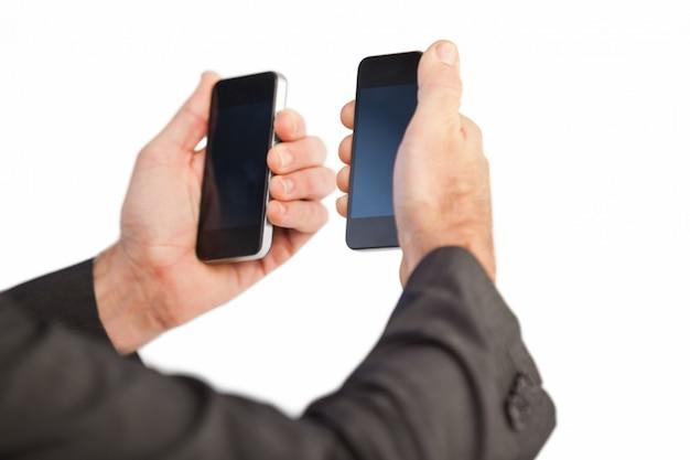 Zakenman die een telefoon in elke hand houdt