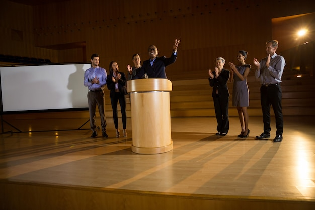 Zakenman die een toespraak houdt terwijl collega's bij conferentiecentrum applaudisseren