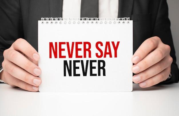 Zakenman die een vel papier vasthoudt met de boodschap nooit zeggen nooit
