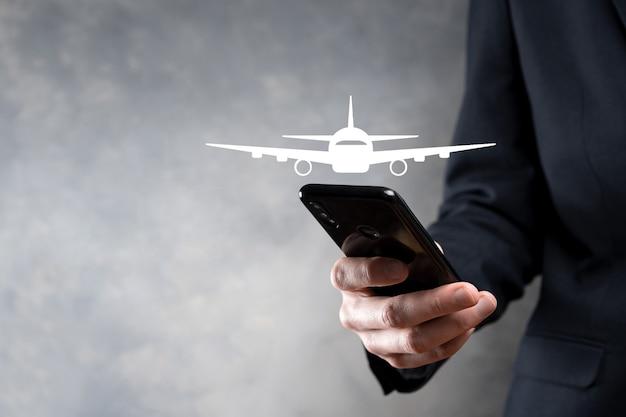 Zakenman die een vliegtuigpictogram in zijn handen houdt. online kaartaankoop. reizen. Premium Foto