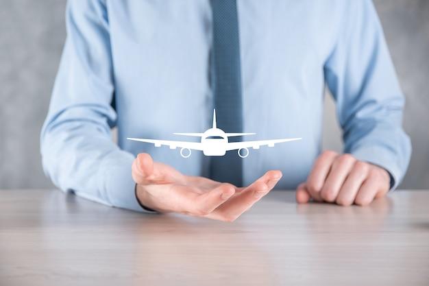 Zakenman die een vliegtuigpictogram in zijn handen houdt
