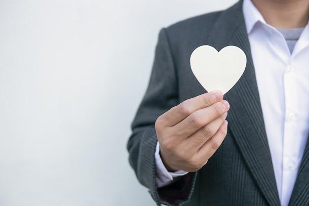 Zakenman die een wit hart geeft aan een klant op wit