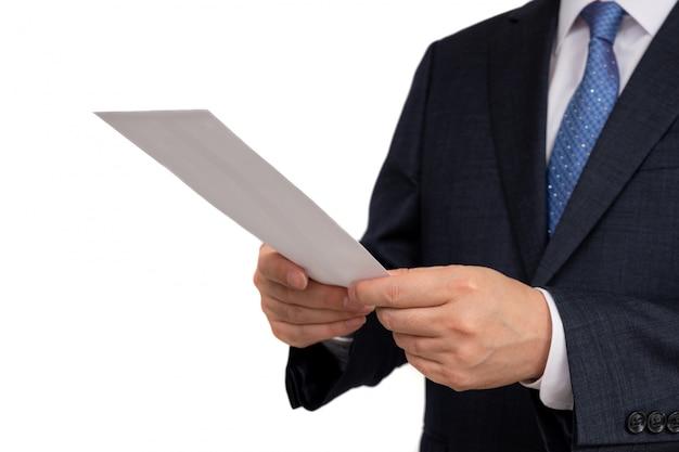 Zakenman die een witte envelop in zijn hand houdt.