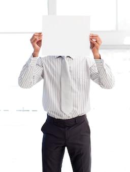 Zakenman die een witte kaart houdt die zijn gezicht behandelt